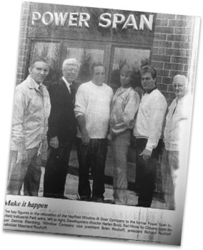 Newspaper clipping of an image of the leadership team standing in front of our newly expanded space